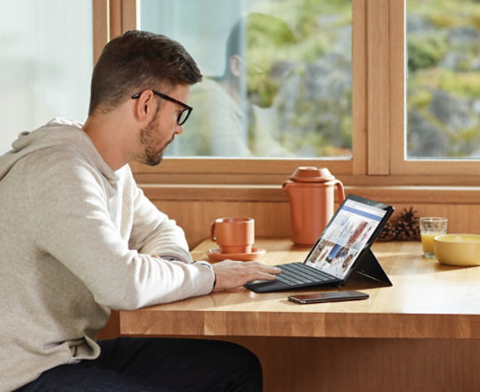A person works at home using a Surface device.