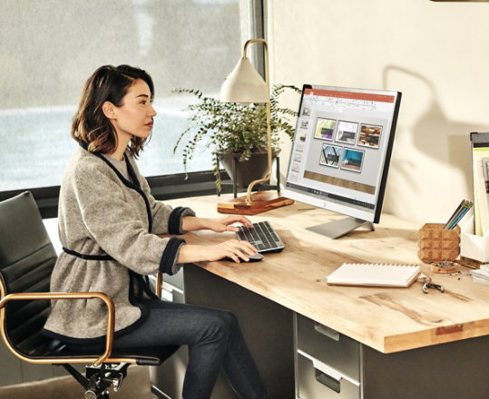 A woman using Office applications on her Windows device at a desk.