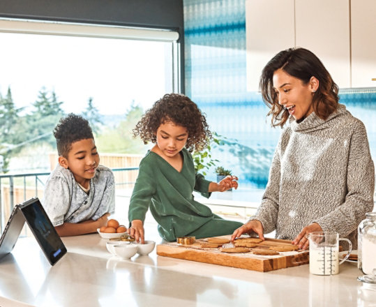 A family gathers around a Surface device while making cookies in their kitchen.