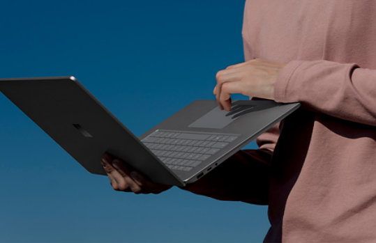 Person using holding Surface Laptop 3 while using the trackpad.