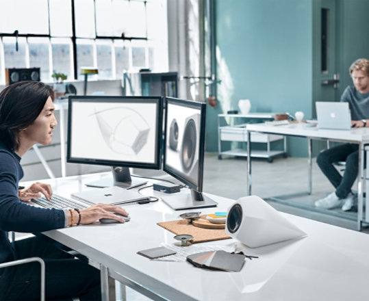 A man uses his Surface Mouse with a Windows device at a desk.
