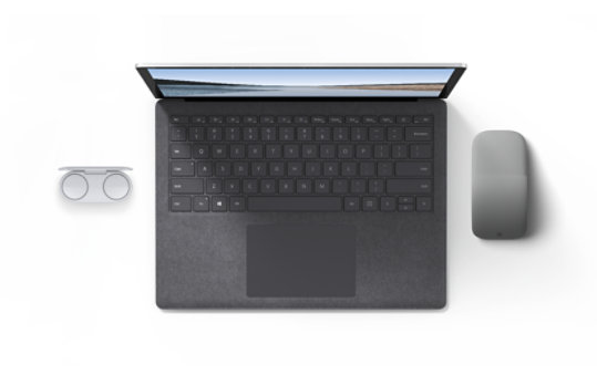 A Surface Laptop next to Surface Earbuds and a Surface Arc Mouse.