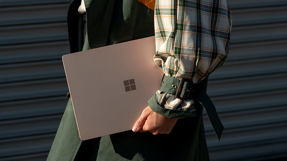 A person carries the Surface Laptop 3 with them on the go.