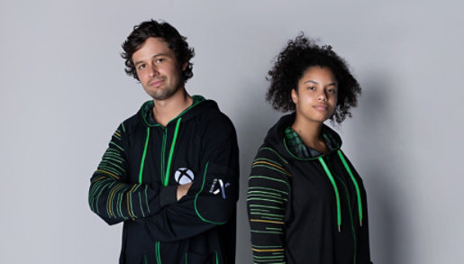 Two people wearing Xbox Series X Hooded Union Suits.