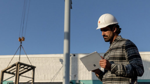 A worker uses a Surface device at a construction site.