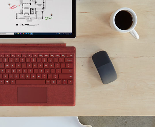 A Microsoft Arc Mouse sits on a desk next to a Surface device.