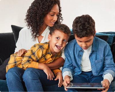 Parent tenant un enfant tandis qu'un autre enfant utilise une tablette
