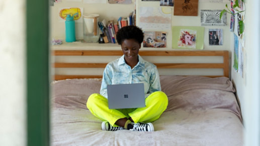 A person uses Surface Laptop Go while sitting on her bed.