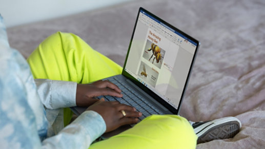 A person uses Surface Laptop Go to edit documents.
